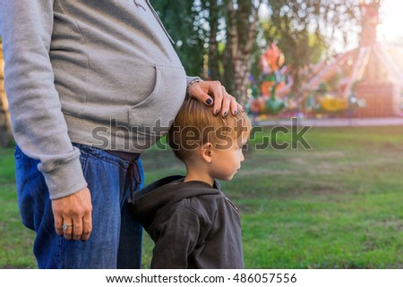 Pregnant mother and her son standing in the park, a female hand holding the boy's head, leaning against her tummy.