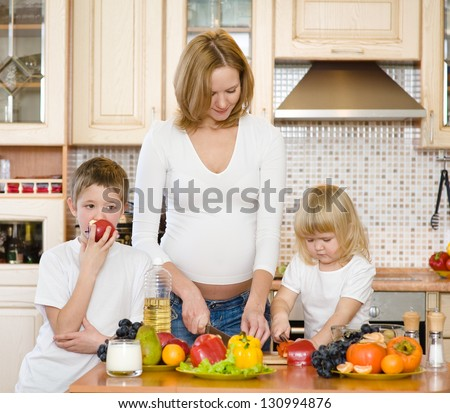 pregnant mother and kids in kitchen - stock photo