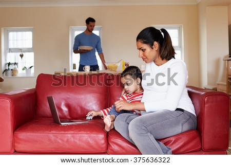 Pregnant Mother Looks At Laptop On Sofa With Son - stock photo