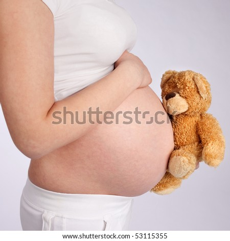 Pregnant mother showing her belly and holding a teddy bear