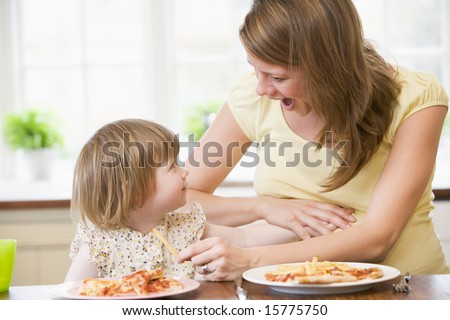 Pregnant mother with daughter touching belly eating French fries and pizza - stock photo