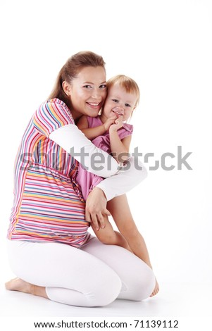 Pregnant mother with her small daughter studio shot - stock photo