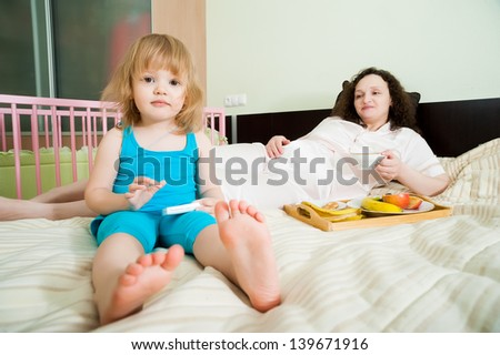 Pregnant mother with 2 years old daughter eating fruits in bedroom - stock photo