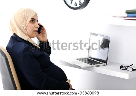 Pregnant Muslim Arabic business woman speaking on phone - stock photo