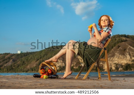 Pregnant red haired woman is sitting on the chair and eating corn.