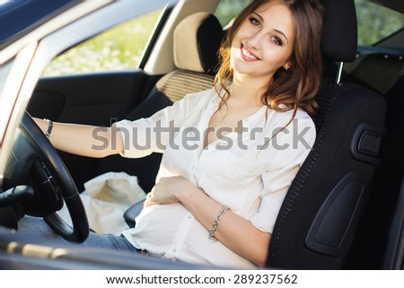Pregnant smiling pretty woman in sitting at the wheel in car, sunset time