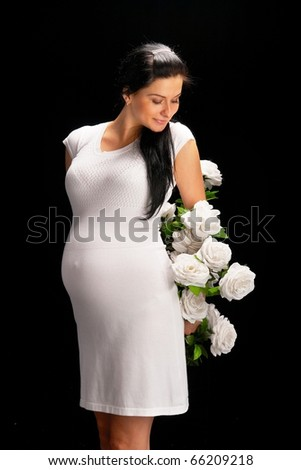 pregnant with roses on black - stock photo