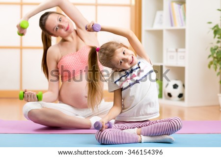 Pregnant woman and her elder child daughter doing fitness exercises  with dumbbells