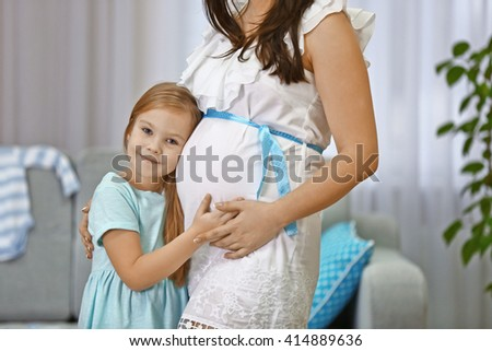 Pregnant woman and her happy child hugging
