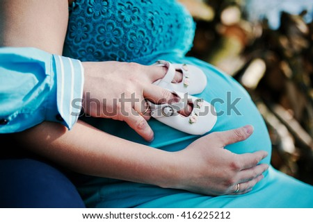 Pregnant woman and her husband holding hands on tummy with girls baby shoes. New life theme - stock photo