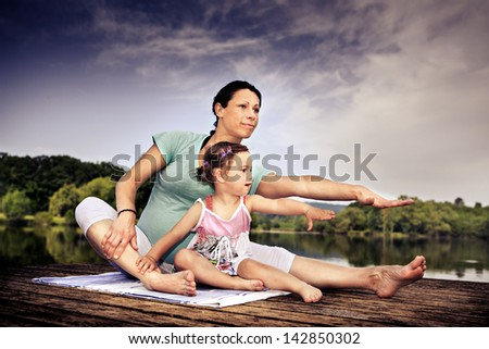 pregnant woman and her little daughter making yoga exercise at a lake - stock photo