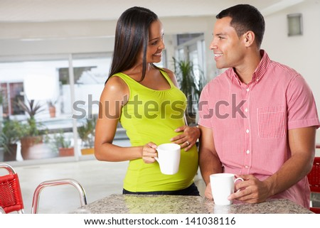 Pregnant Woman And Husband Having Breakfast In Kitchen - stock photo