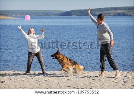Pregnant woman and man playing with german sheep-dog - stock photo
