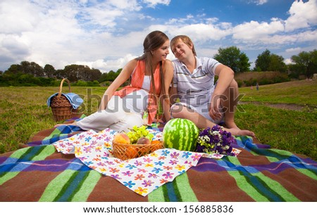Pregnant woman and man relaxing on picnic - stock photo