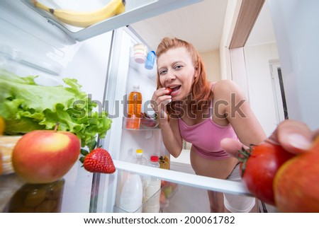 pregnant woman and refrigerator with health food vegetables and fruits - stock photo