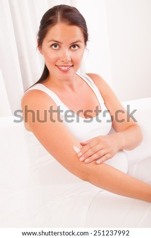 Pregnant woman applying cream on her body - stock photo