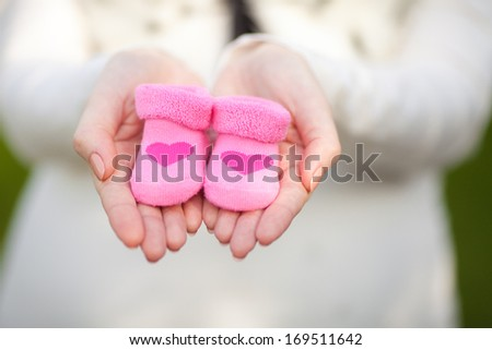 Pregnant woman belly holding pink baby booties, expecting girl. Healthy pregnancy.