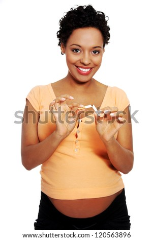 Pregnant woman breaking a cigarette - stop smoking concept - stock photo