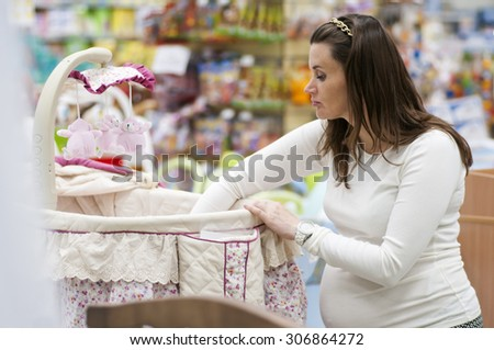 pregnant woman choosing cot for baby - stock photo