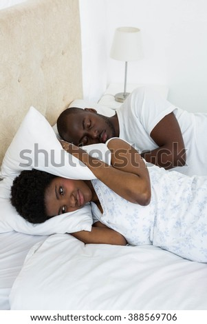 Pregnant woman covering her ears while man snoring - stock photo
