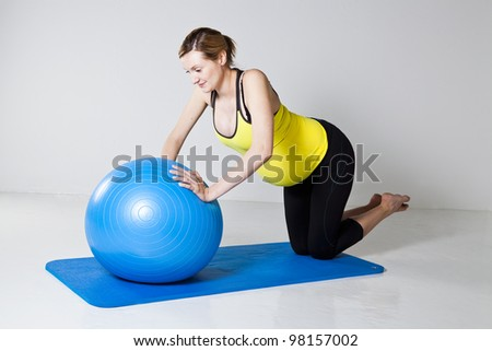 Pregnant woman doing a chest muscle strengthening push-up exercise on a fitness ball - stock photo