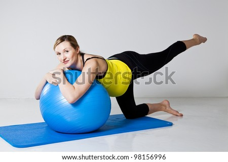 Pregnant woman doing a leg raise strengthening exercise while leaning on a fitness ball on a mat - stock photo