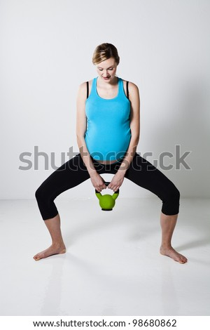 Pregnant woman doing a squatting exercise with a kettlebell - stock photo