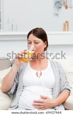 Pregnant woman drinking orange juice on her sofa - stock photo