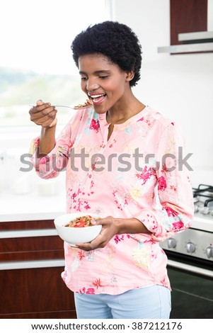 Pregnant woman eating cereal in kitchen