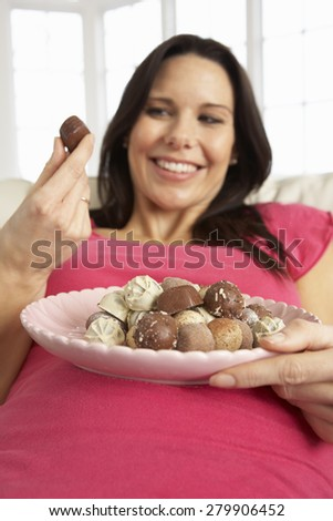 Pregnant Woman Eating Chocolates Sitting On Sofa At Home - stock photo