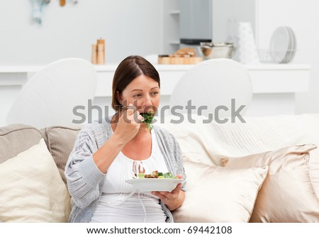 Pregnant woman eating vegetables on her sofa - stock photo