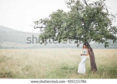 Pregnant woman enjoying summer park, wearing long white dress, holding in hands bouquet of flowers, outdoors, new life concept. fresh mood