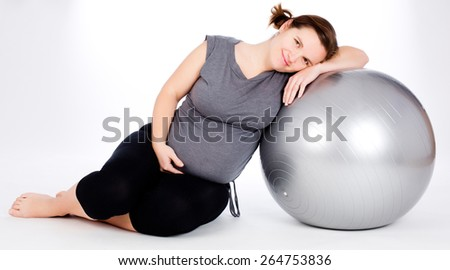 Pregnant woman excercises with big gray gymnastic ball.