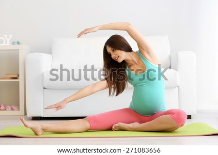 Pregnant woman exercising on green mat in room - stock photo