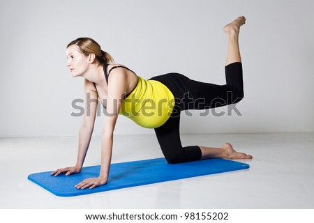 Pregnant woman exercising on mat to develop balance and muscular strength of the core trunk and leg muscles - stock photo