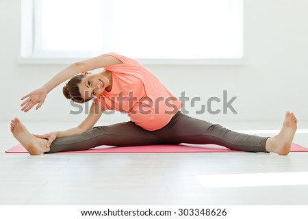 Pregnant woman exercising yoga on the mat - stock photo