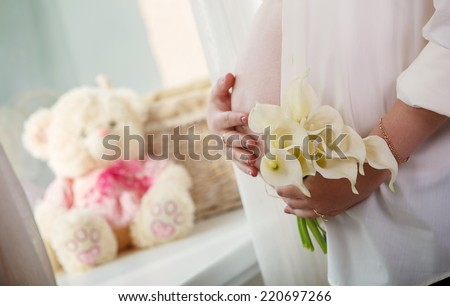 Pregnant woman gently stroking his tummy Pregnant woman embracing her belly delicate bouquet of white calla in the hands of pregnant girl - stock photo