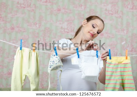 Pregnant woman hanging children's clothes on rope at home. - stock photo