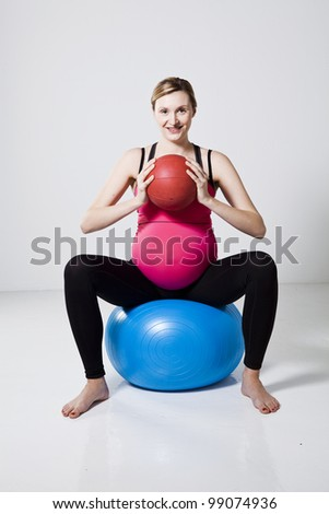 Pregnant woman holding a red exercise ball to exercise while sitting on a blue fitness ball - stock photo