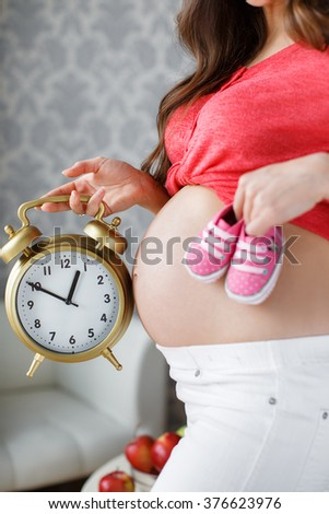Pregnant woman holding alarm clock. Pregnant woman's belly. closeup of a pregnant woman holding an alarm-clock near her belly at home in bedroom.  - stock photo