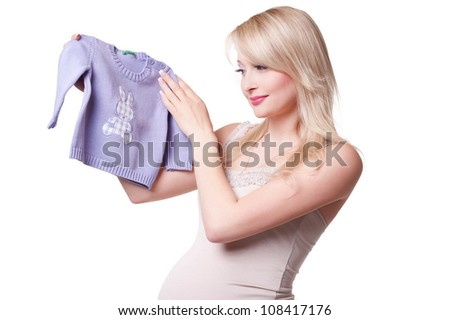 Pregnant woman holding baby clothing - stock photo