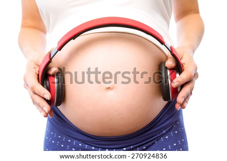 Pregnant woman holding earphones over bump on white background - stock photo