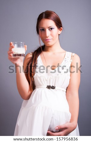pregnant woman holding glass of milk - stock photo