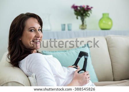 Pregnant woman holding headphone on belly in living room