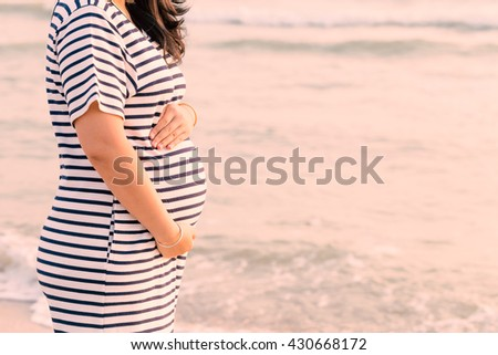 Pregnant woman holding her belly on the beach with copy space in the morning time. (Vintage tone) - stock photo