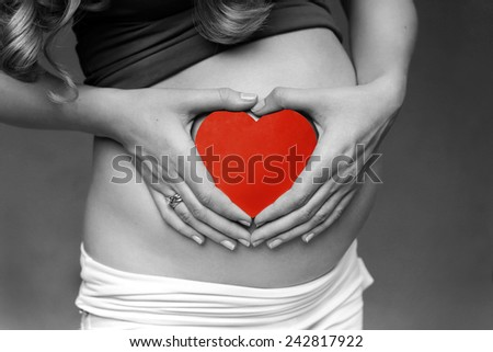 Pregnant Woman holding her hands in a heart shape on her baby bump. Pregnant Belly with fingers Heart symbol. Maternity concept. Woman expecting a baby holding a red heart with love. - stock photo