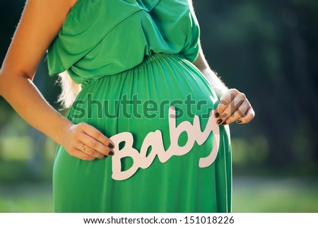 Pregnant woman holding  word BABY - stock photo