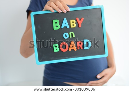Pregnant woman holds a baby on board colored text on blackboard over her belly - stock photo
