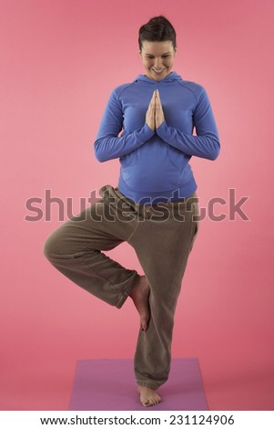 Pregnant Woman in a Standing Yoga Position - stock photo