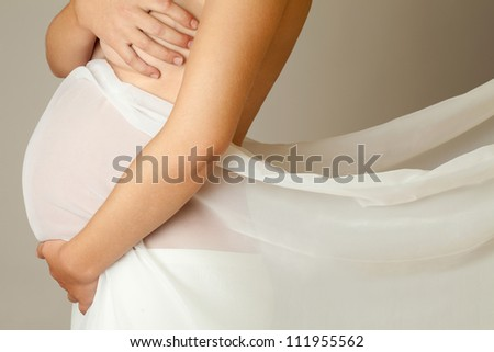 Pregnant woman in a white tulle - stock photo